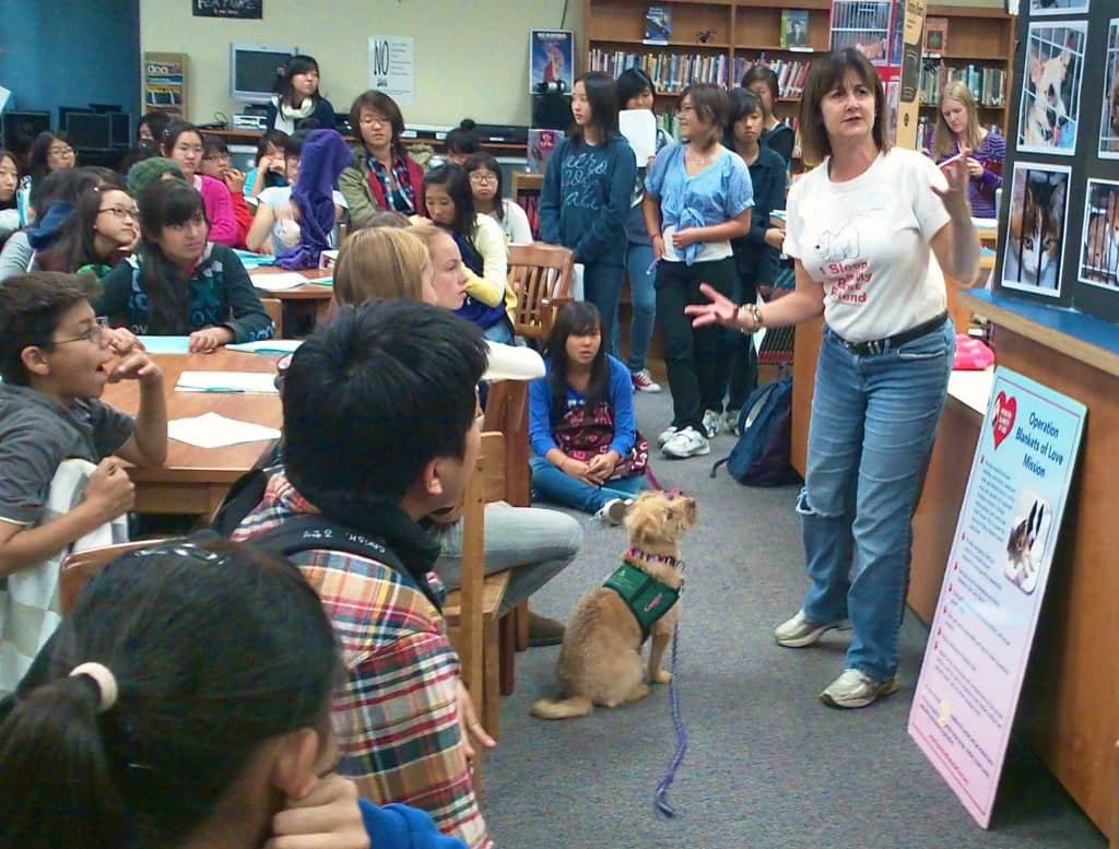 Eileen and Ginger presenting to high school students how to respect and be kind to all animals.