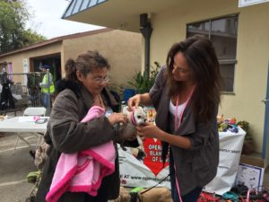 OBOL's Clarissa fits a harness on a homeless lady's chihuahua.  The little dog also got a blanket, food and treats.
