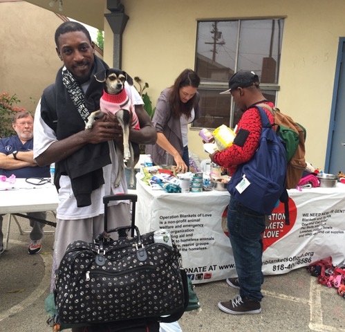 Homeless men are happy to get pet supplies donated to them from OBOL.